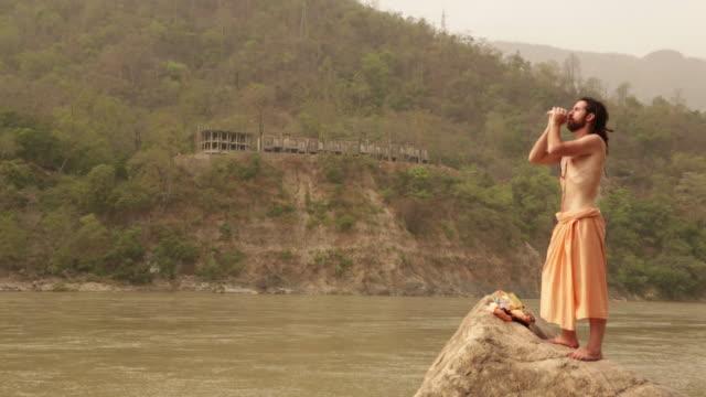 vídeos de stock e filmes b-roll de sage blowing conch shell at ganges riverbank, rishikesh, uttarakhand, india - concha do mar