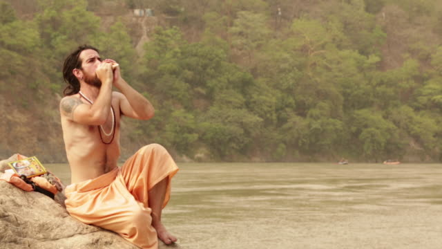 sage blowing conch shell at ganges riverbank, rishikesh, uttarakhand, india - guru stock videos & royalty-free footage