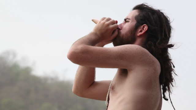 sage blowing conch shell, rishikesh, uttarakhand, india - conch stock videos & royalty-free footage