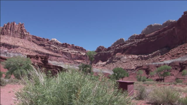 sage brush grows at the base of red rock formations. - セージブラッシュ点の映像素材/bロール