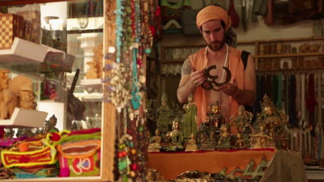 vídeos de stock, filmes e b-roll de sage buying om symbol at market, rishikesh, uttarakhand, india - rishikesh