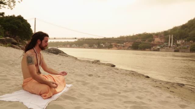 vídeos de stock, filmes e b-roll de sage doing padmasana at ganges riverbank, laxman jhula, rishikesh, uttarakhand, india - só um adulto de idade mediana