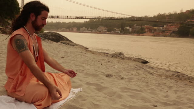 Sage doing padmasana at ganges riverbank, Laxman Jhula, Rishikesh, Uttarakhand, India