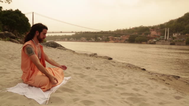 Sage doing padmasana at ganges riverbank, Laxman Jhula, Rishikesh, Uttarakhand, India