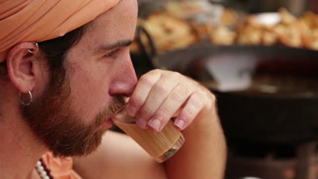 vídeos de stock, filmes e b-roll de sage drinking tea at market, rishikesh, uttarakhand, india - rishikesh