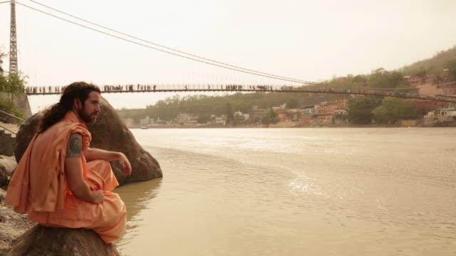 vídeos de stock, filmes e b-roll de sage sitting at ganges riverbank, laxman jhula, rishikesh, uttarakhand, india - rishikesh