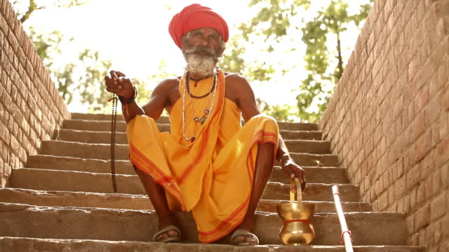 sage with prayer beads sitting on stairs, faridabad, haryana, india - guru stock videos & royalty-free footage