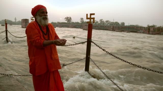 Sage worshipping at riverbank, Ganges River, Haridwar, Uttarakhand, India