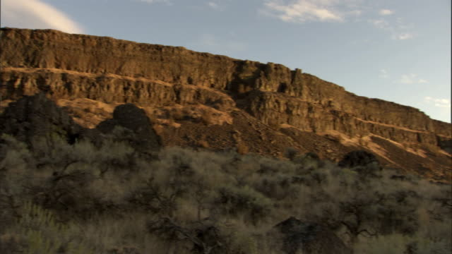 Sagebrush covers the hillside at the foot of rock formations in the Scablands. Available in HD.