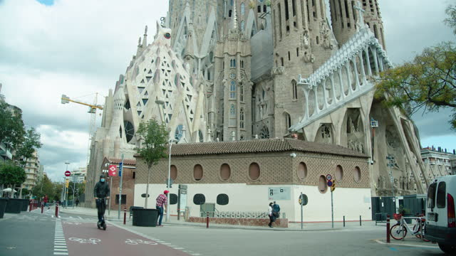 sagrada familia barcelona during covid-19 crisis. people using electric scooter wearing mask - basilica stock videos & royalty-free footage