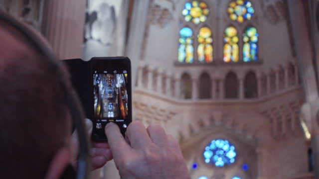 Sagrada Familia, tourist taking picture with a phone. Barcelona cathedral by Gaudi. Ceiling, columns and colorful stained glass windows. Wolrd famous artistical architecture from Modernism in Catalonia.