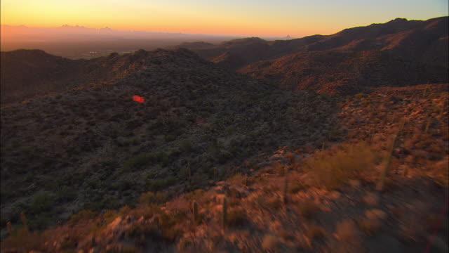 LOW AERIAL Saguaro cactus covered mountains at sunset, Tucson, Arizona, USA