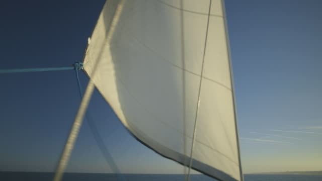 A sail is unfurled on a moving yacht off the south coast of England, UK.