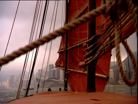 sail mast and rigging of traditional junk rise and fall in swell skyscrapers in background hong kong - rigging stock videos & royalty-free footage