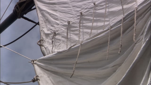 Sail of replica of HMS Endeavour billows in breeze.