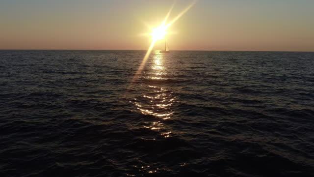 vidéos et rushes de voilier contre le coucher de soleil sur l'horizon - horizon over water