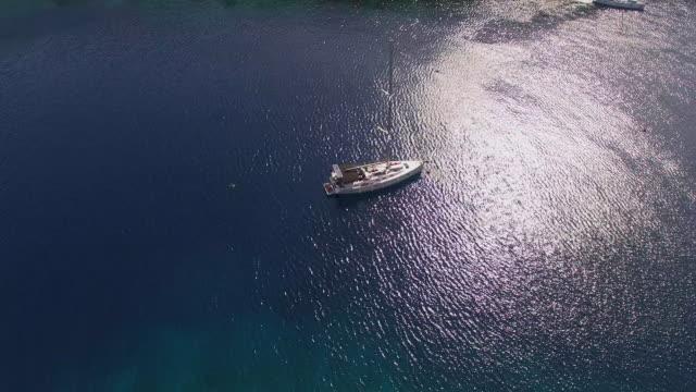 luftbild segelboot vor anker in der bucht - segeljacht stock-videos und b-roll-filmmaterial