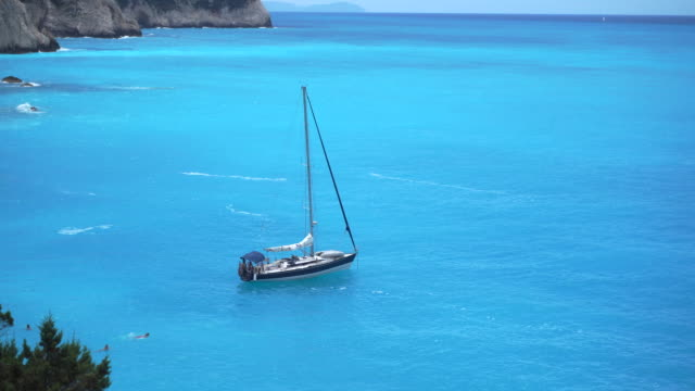 sailboat anchored off the coast - stationary stock videos & royalty-free footage