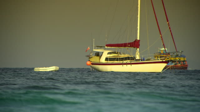ms sailboat anchored on sea, boat moving in background, krabi, thailand - see other clips from this shoot 1459 stock videos and b-roll footage