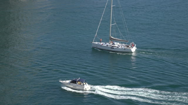 a sailboat and a motorboat driving side by side in sea - side by side stock videos & royalty-free footage