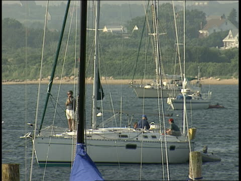 a sailboat approaches a pier crowded with vacationers. - 船の一部点の映像素材/bロール