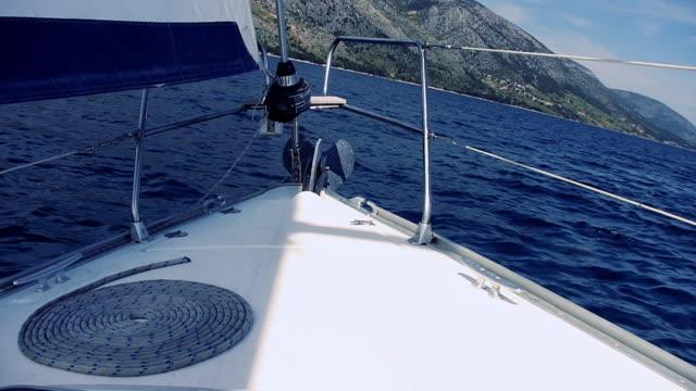 hd: barca a vela avvicinarsi costa - barca da diporto video stock e b–roll