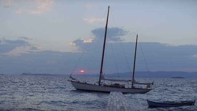 stockvideo's en b-roll-footage met ws sailboat at anchor, dock and rowboat in foreground / greece   - voor anker gaan