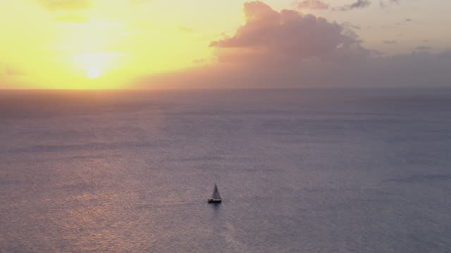 Sailboat at sea under peaceful sunset.