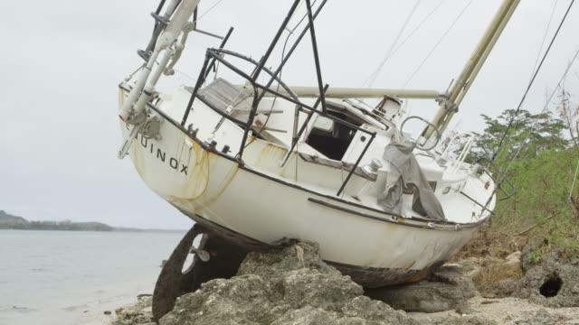 vanuatu - march 29, 2015: cu sailboat beached after cyclone pam - gestrandet stock-videos und b-roll-filmmaterial
