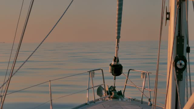 sailboat bow in tranquil waters of calm sea in the atlantic ocean at sunset. view of sail and rigs - yacht stock videos & royalty-free footage