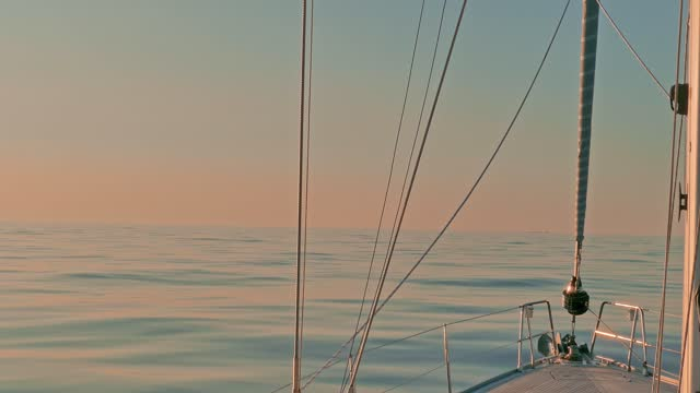 sailboat bow in tranquil waters of calm sea in the atlantic ocean at sunset. view of sail and rigs - ship's bow stock videos & royalty-free footage