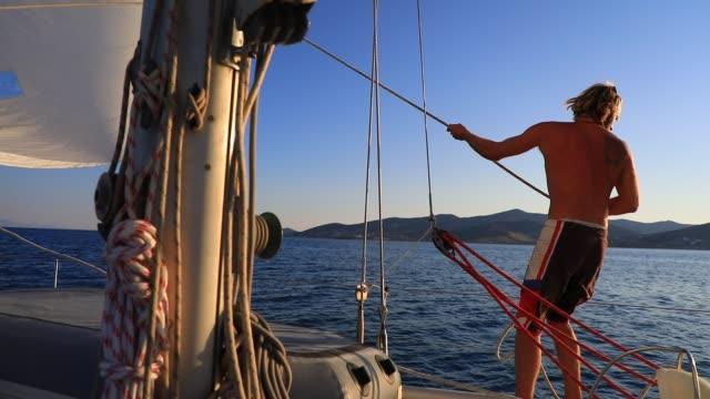 vidéos et rushes de sailboat captain hoist the mainsail on the aegean sea on august 19, 2020 in parikia, greece. the island of paros has seen increasing tourist numbers... - équipe de voile
