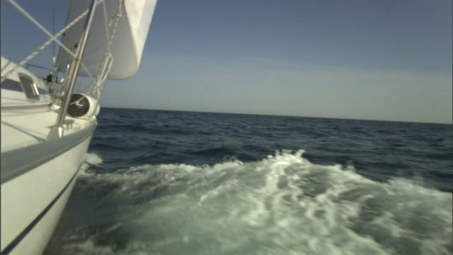 a sailboat cruises out to the open sea. - sailing boat stock videos & royalty-free footage