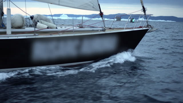 a sailboat cuts through dark choppy waters at dusk on disko bay - rigging nautical stock videos & royalty-free footage