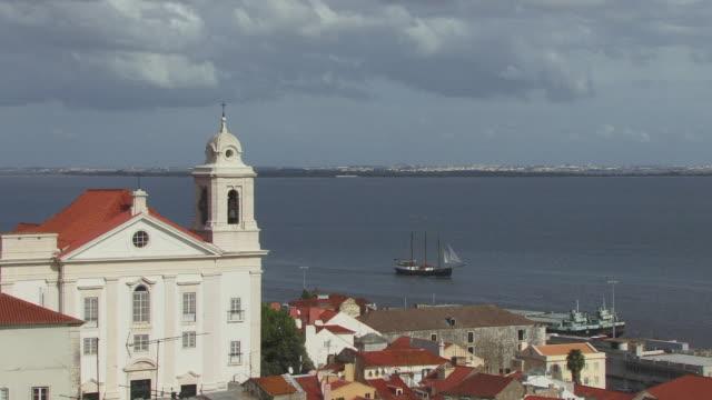 HA WS ZO Sailboat floating past Santo Estevao Church and cityscape / Lisbon, Portugal