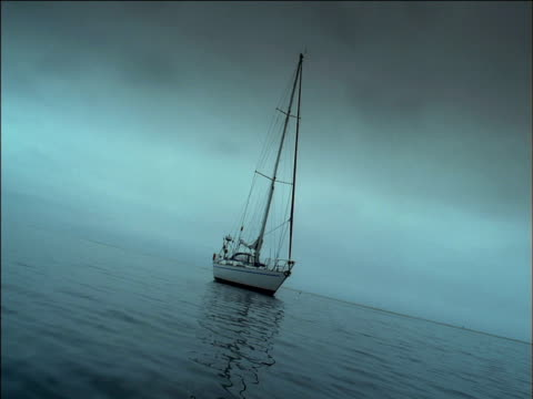 sailboat floats at anchor on still grey ocean, south africa - tauwerk stock-videos und b-roll-filmmaterial