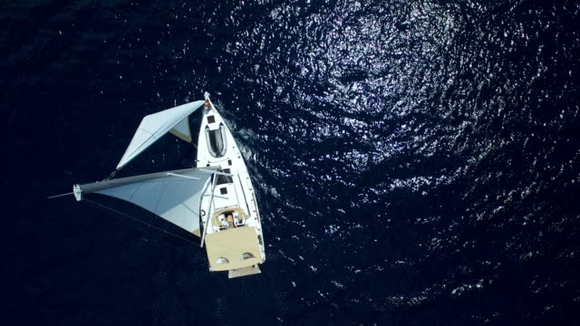 vídeos de stock e filmes b-roll de sailboat from above, shot from drone - vela desporto aquático