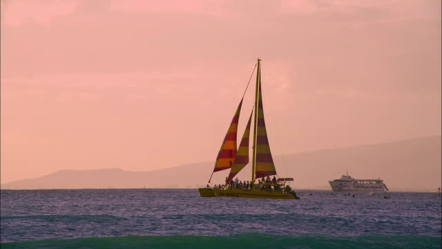 A sailboat gently glides through the waters of the Pacific Ocean near Hawaii.