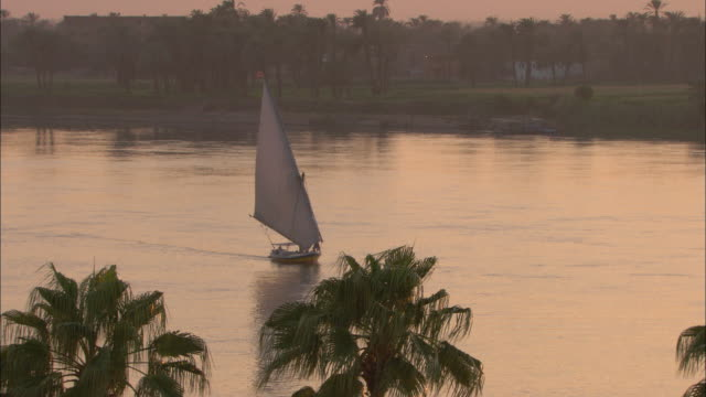 A sailboat glides along the Nile River.