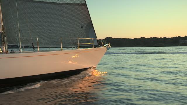 a sailboat glides through narragansett bay at sunset. - ship's bow stock videos & royalty-free footage