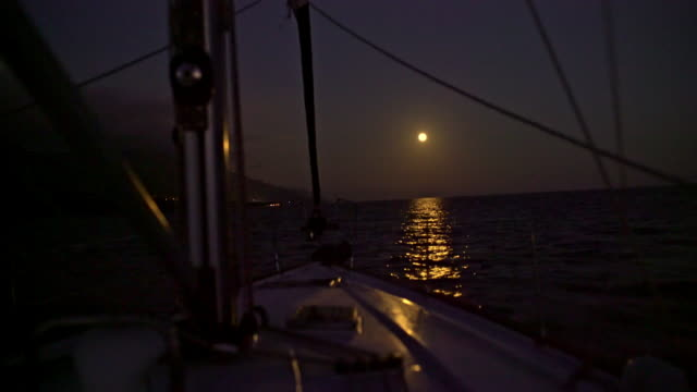 4k sailboat heading towards full moon shining over tranquil night ocean, real time - sailing stock videos & royalty-free footage