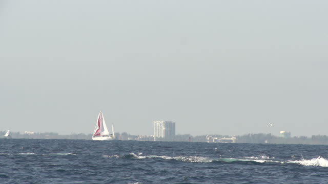 sailboat in distance behind rough surf - surf fishing stock videos & royalty-free footage