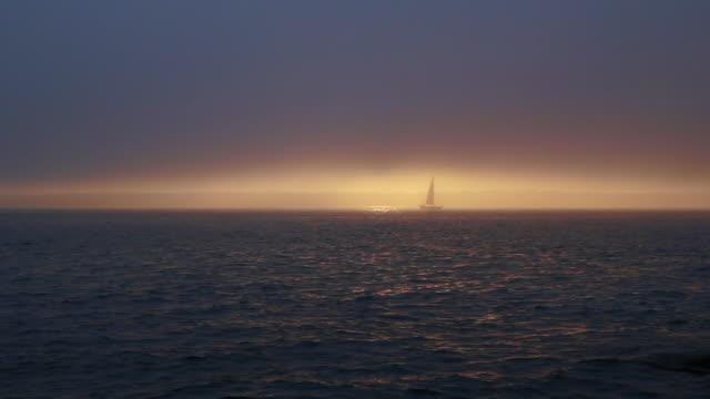 vídeos de stock e filmes b-roll de sailboat in the fog wrapped sunset - 1 minuto ou mais
