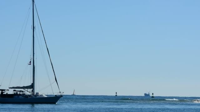 sailboat motors through frame, oil rigs are on the horizon in the santa barbara channel. boat headed for harbor. sunny afternoon santa barbara beach,... - santa barbara california stock videos & royalty-free footage