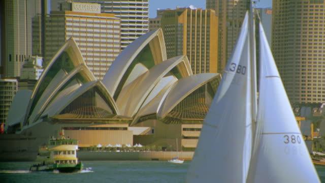 Sailboat moving in harbor to reveal Sydney Opera House + city skyline / Sydney, Australia