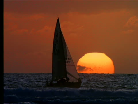 sailboat on ocean with large sunset in background - romantische stimmung stock-videos und b-roll-filmmaterial