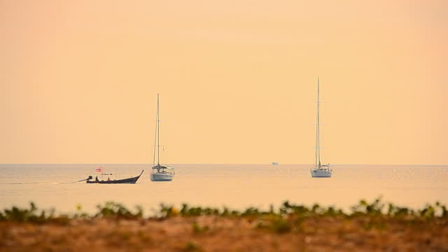 Sailboat on tropical sunset beach
