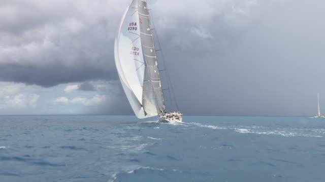 a sailboat races through the caribbean sea in the st. maarten heineken regatta. - gara sportiva video stock e b–roll