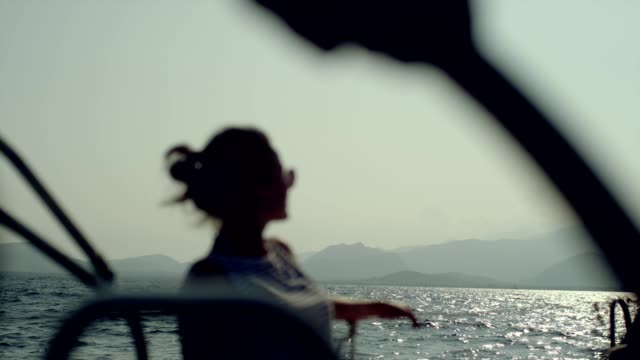 sailboat relaxation. woman enjoying sun and sailing - sail stock videos & royalty-free footage