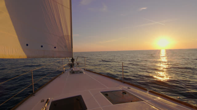 slo mo sailboat sailing at sunset - sailing boat stock videos and b-roll footage